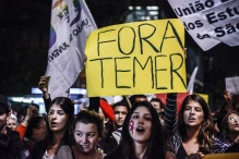 Protesters hold signs and chant in opposition to Michel Temer, Brazil's acting president, in Sao Paulo, Brazil, on Tuesday, May 17, 2016. Temer said he will only gain popular recognition if he produces tangible results for the population, while pledging not to run for the country's top job in the 2018 election. Photographer: Paulo Fridman/Bloomberg via Getty Images